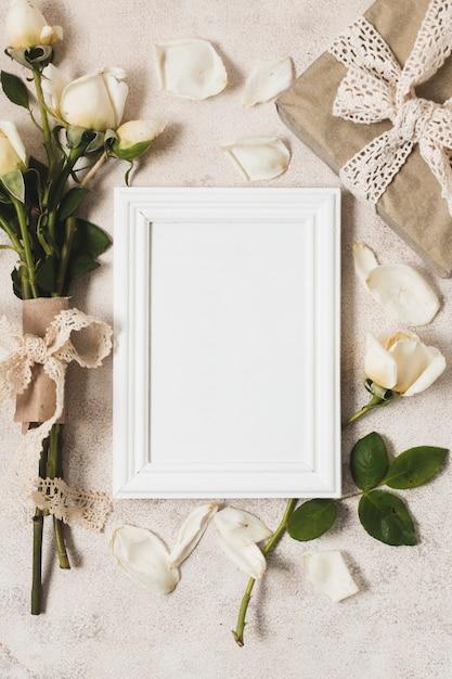 Vue de dessus du cadre avec cadeau et bouquet de rose Photo gratuit