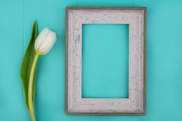Vue De Dessus Du Cadre Et De La Fleur Sur Fond Bleu Avec Espace Copie Photo gratuit