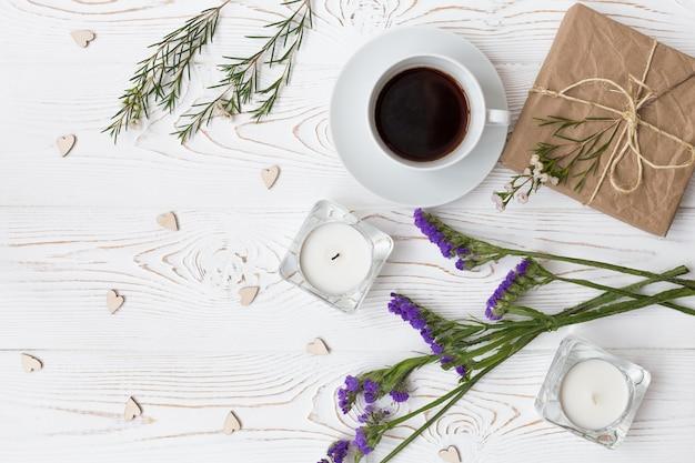 Vue de dessus du café, des cadeaux, des coeurs, des bougies, des fleurs sur woode blanc Photo Premium