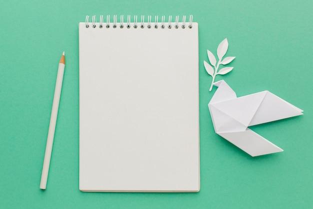Vue De Dessus Du Cahier Avec Colombe Papier Et Crayon Photo gratuit
