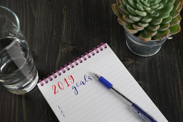 Vue de dessus du cahier avec objectifs de texte 2019 et liste de tâches avec espace de copie Photo Premium