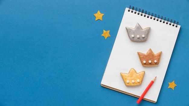 Vue De Dessus Du Cahier Avec Trois Couronnes Et étoiles Pour Le Jour De L'épiphanie Photo gratuit