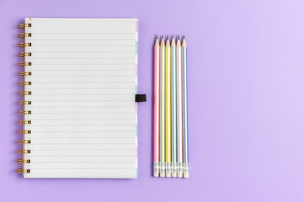 Vue De Dessus Du Cahier Vierge Avec Des Crayons Sur Fond Pastel Violet Photo Premium