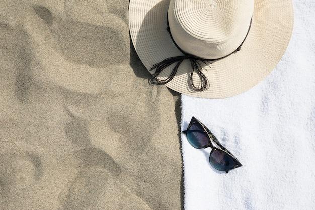 Vue de dessus du chapeau sur une serviette de plage Photo gratuit