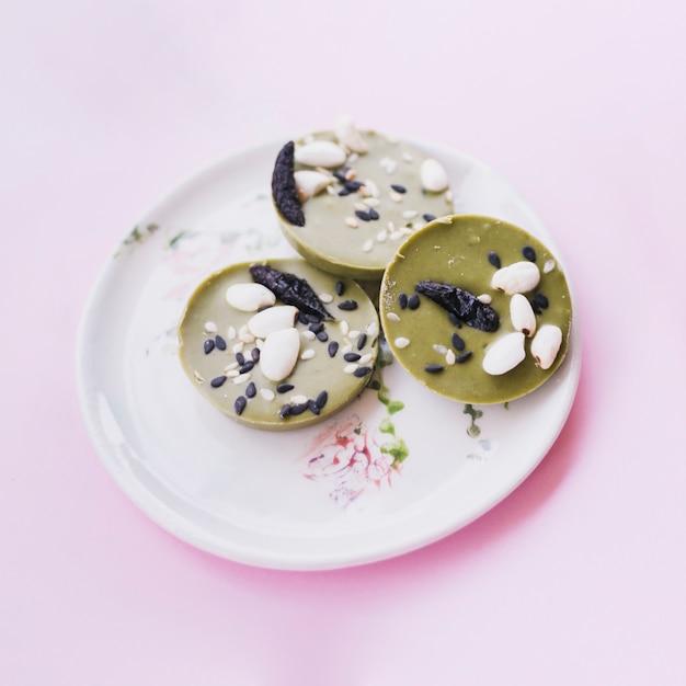 Vue de dessus du chocolat rond vert avec garniture aux graines de sésame et d'arachide Photo gratuit