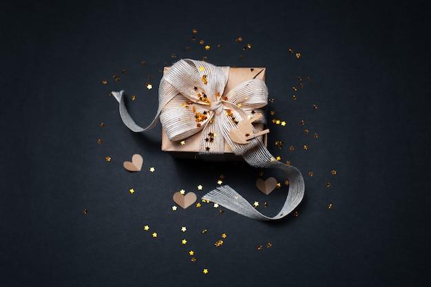 Vue De Dessus Du Coffret Cadeau écologique Décoré D'étoiles Dorées Et De Papiers En Forme De Coeurs, Sur Une Surface De Couleur Noire Photo Premium