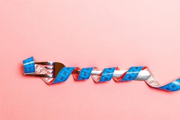 Vue de dessus du concept d'obésité avec fourche enveloppée dans du ruban à mesurer sur bleu Photo Premium