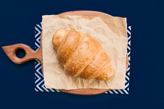 Vue De Dessus Du Croissant Sur Une Planche à Découper Et Du Papier Kraft Sur Fond Bleu Avec Espace De Copie. Photo Premium