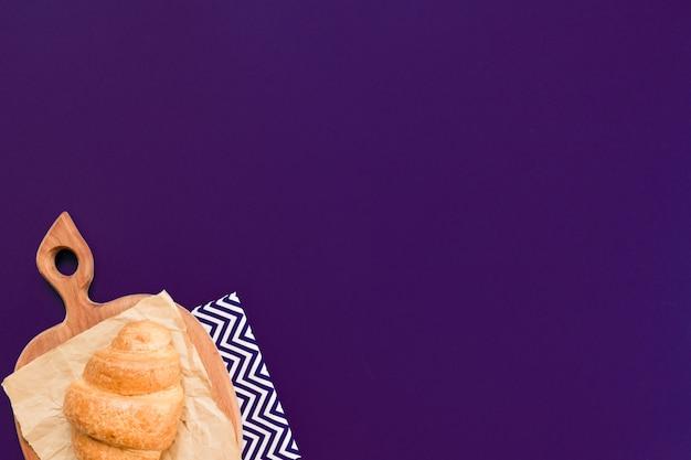 Vue De Dessus Du Croissant Sur Une Planche à Découper Et Du Papier Kraft Sur Fond Outremer Avec Copie Espace. Photo Premium