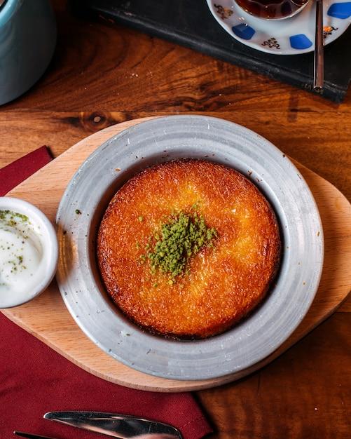 Vue De Dessus Du Dessert Turc Traditionnel Kunefe Avec De La Poudre De Pistache Sur Une Table En Bois Photo gratuit