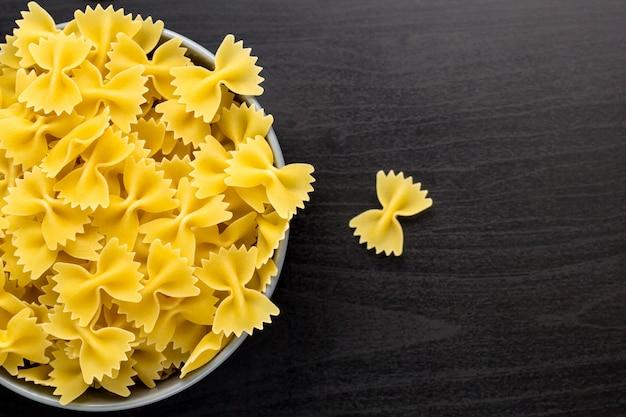 Vue de dessus du fond noir avec farfalle italien brut ou des pâtes dans un bol Photo Premium