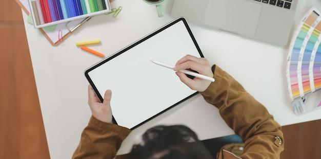 Vue de dessus du graphiste femelle dessinant sur tablette Photo Premium