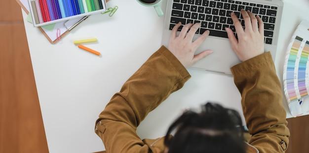 Vue de dessus du graphiste femme en tapant sur le clavier d'ordinateur portable Photo Premium