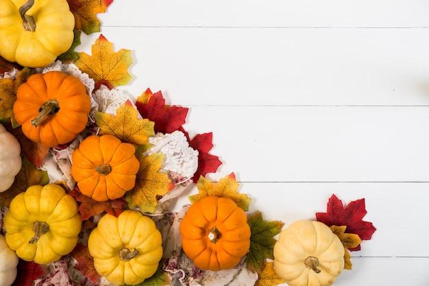 Vue De Dessus Du Jour De L'halloween Ou De Thanksgiving, Citrouilles, Feuilles D'érable Et Pomme De Pin Sur Fond Blanc Avec Espace De Copie Photo Premium