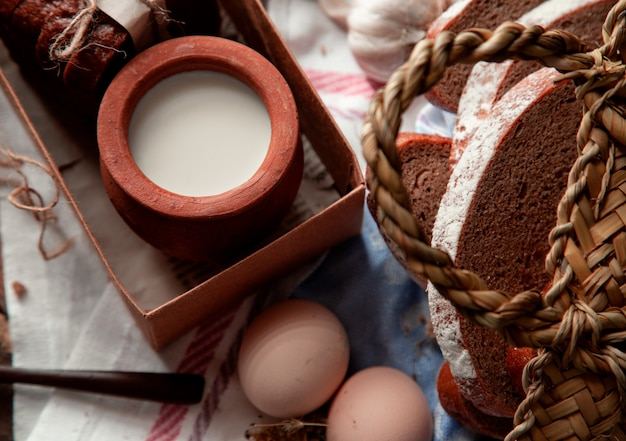 Vue de dessus du lait dans une casserole à l'intérieur d'une boîte, des tranches de pain et des œufs. Photo gratuit