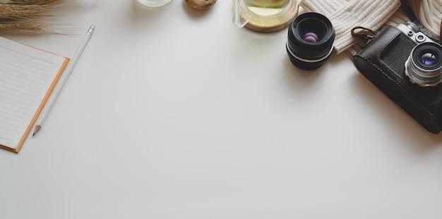 Vue de dessus du lieu de travail minimal avec appareil photo vintage et fournitures de bureau avec des décorations Photo Premium