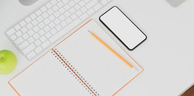 Vue de dessus du lieu de travail minimal avec smartphone écran blanc Photo Premium