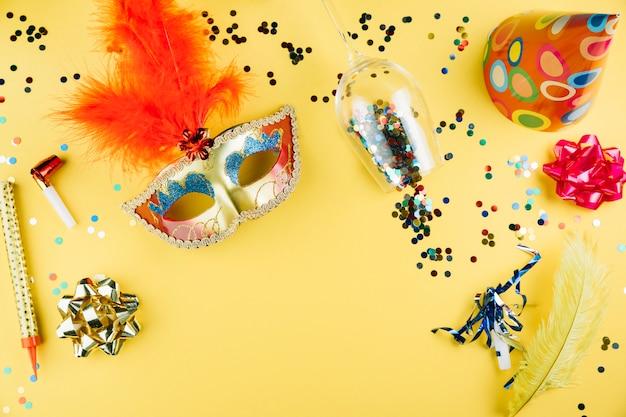 Vue de dessus du masque de carnaval avec du matériel de décoration et sur fond jaune Photo gratuit