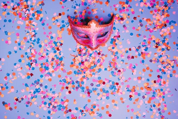 Vue de dessus du masque de carnaval magnifique avec des confettis colorés sur fond bleu Photo gratuit