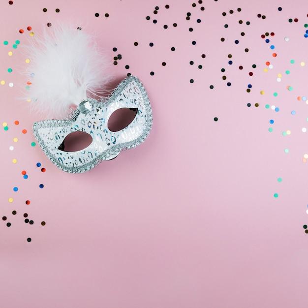 Vue de dessus du masque de carnaval de mascarade avec des confettis colorés sur fond rose Photo gratuit