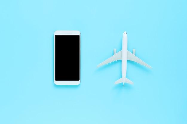Vue de dessus du mobile et avion sur fond bleu isolé avec espace de copie Photo Premium