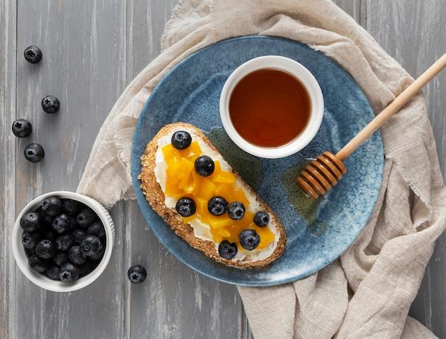 Vue De Dessus Du Pain Avec Du Fromage à La Crème Et Des Fruits Sur Une Assiette Avec Du Miel Photo gratuit