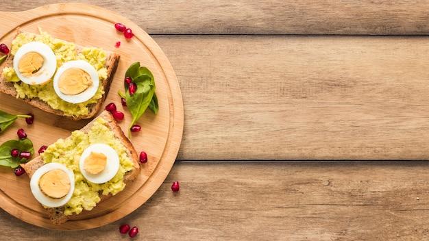 Vue de dessus du pain grillé avec œuf à la coque sur une planche à découper Photo gratuit