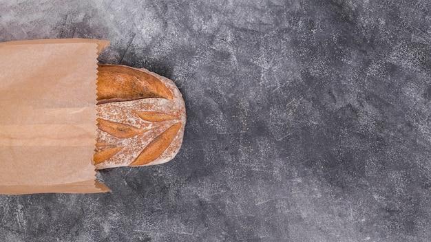Vue de dessus du pain à l'intérieur du sac en papier brun sur fond texturé noir Photo gratuit