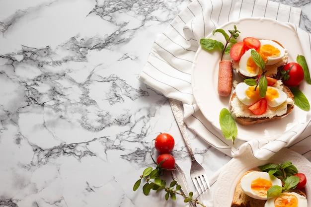 Vue de dessus du pain avec des œufs à la coque, des tomates et des hot-dogs Photo gratuit