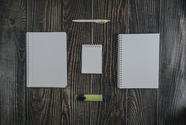 Vue de dessus du papier vierge avec un stylo et un marqueur sur une table en bois marron pour le fond Photo Premium