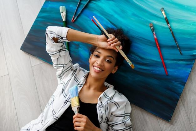 Vue De Dessus Du Peintre Heureux Africana Femme Américaine Couchée Sur Toile Et Regardant La Caméra Avec Des Pinceaux Dans Les Mains. Photo gratuit
