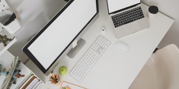 Vue de dessus du poste de graphiste avec un ordinateur portable à écran blanc Photo Premium