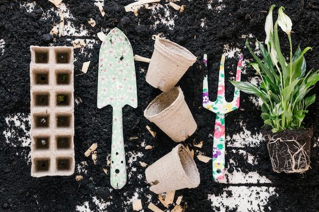 Vue de dessus du pot de tourbe; plateau de tourbe; pelle de jardinage; fourche et plante sur sol noir Photo gratuit