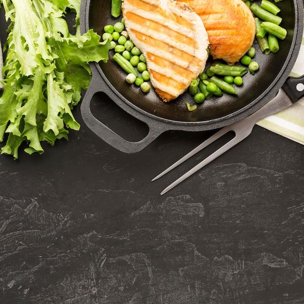 Vue De Dessus Du Poulet Et Des Pois Grillés Dans La Poêle Avec Salade Et Copie-espace Photo gratuit
