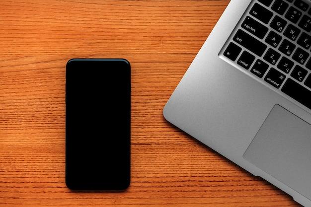 Vue de dessus du processus d'étude avec cahier, livre et ordinateur portable. tasses de café sur la table Photo Premium