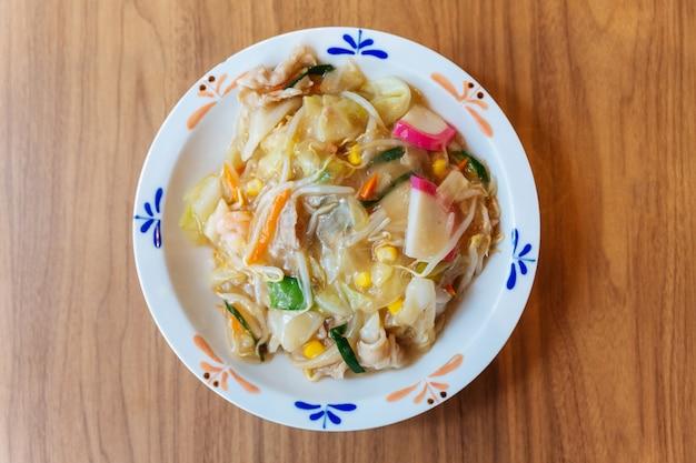 Vue de dessus du ramen champon avec du porc, des crevettes, des oignons verts, du germe, des carottes, du chou, du maïs et du kamaboko. Photo Premium
