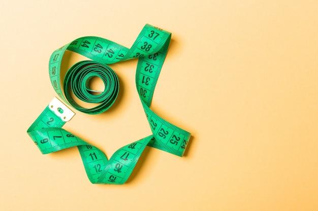 Vue de dessus du ruban de mesure réduit en spirale avec espace de copie. accessoire de couture ou alimentation saine sur orange Photo Premium