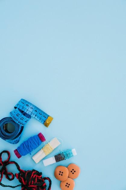 Une vue de dessus du ruban à mesurer; la laine; bobines et boutons sur le coin de fond bleu Photo gratuit