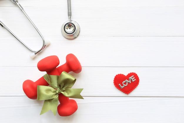 Vue de dessus du ruban vert avec haltères et stéthoscope de coeur en bonne santé sur fond blanc en bois Photo Premium