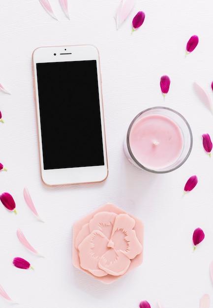 Une vue de dessus du savon en forme de fleur; bougie et smartphone décorés de pétales Photo gratuit