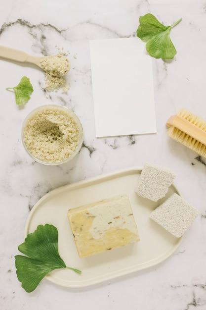 Vue de dessus du savon; sel; pierre ponce; brosse; feuille de ginkgo et carte vierge sur fond de marbre Photo gratuit