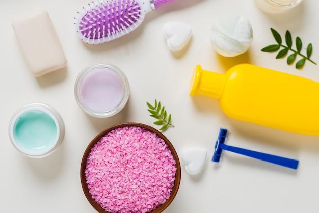 Une vue de dessus du sel rose avec des produits cosmétiques sur fond blanc Photo gratuit