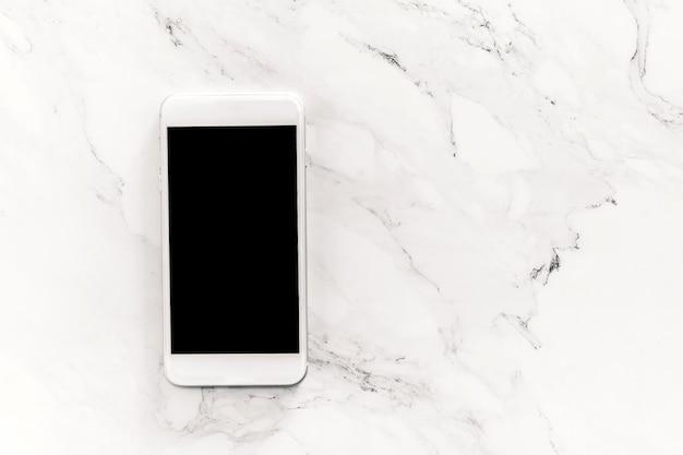Vue de dessus du smartphone de la maquette avec des écrans vierges sur fond de marbre blanc. Photo Premium