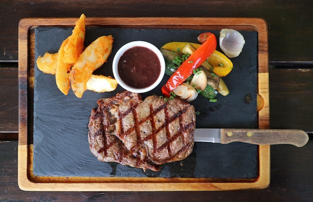Vue de dessus du steak ribeye grillé avec sauce au vin rouge servi sur plaque de pierre chaude Photo Premium