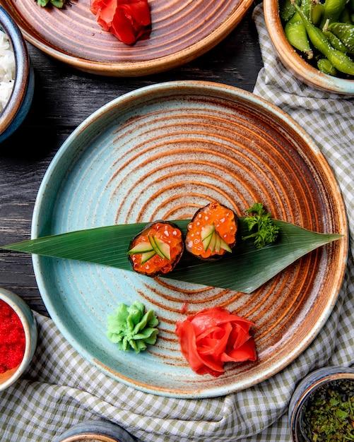 Vue De Dessus Du Sushi Japonais Classique Avec Du Caviar Rouge Sur Une Feuille De Bambou Servi Avec Du Gingembre Et De La Sauce Wasabi Sur Une Assiette Photo gratuit