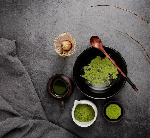 Vue de dessus du thé matcha avec des branches et une cuillère en bois Photo gratuit