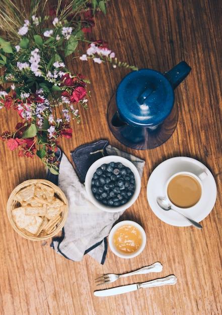 Une vue de dessus du vase; myrtilles; des craquelins; confiture; tasse à café et théière sur fond en bois Photo gratuit