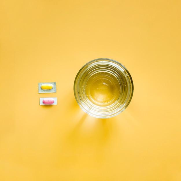 Vue De Dessus Du Verre D'eau Et Des Pilules En Aluminium Photo gratuit