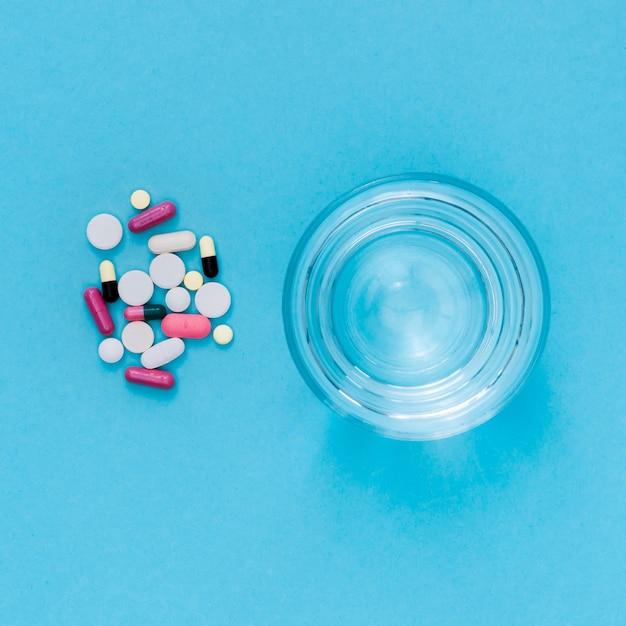 Vue De Dessus Du Verre D'eau Avec Des Pilules Photo gratuit