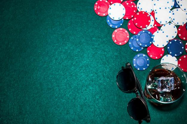 Vue de dessus du verre à whisky; lunettes de soleil et jetons de casino sur la table de poker Photo gratuit